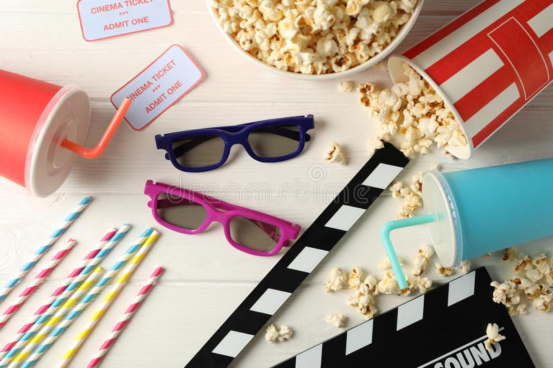 Flat lay. 3d glasses, buckets with popcorn, tickets, clapperboard, drink, on white wood. Background royalty free stock images