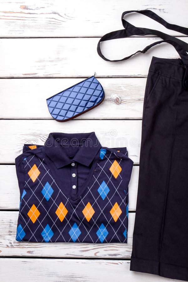 Flat lay decorated polo shirt and blue wallet. royalty free stock photos
