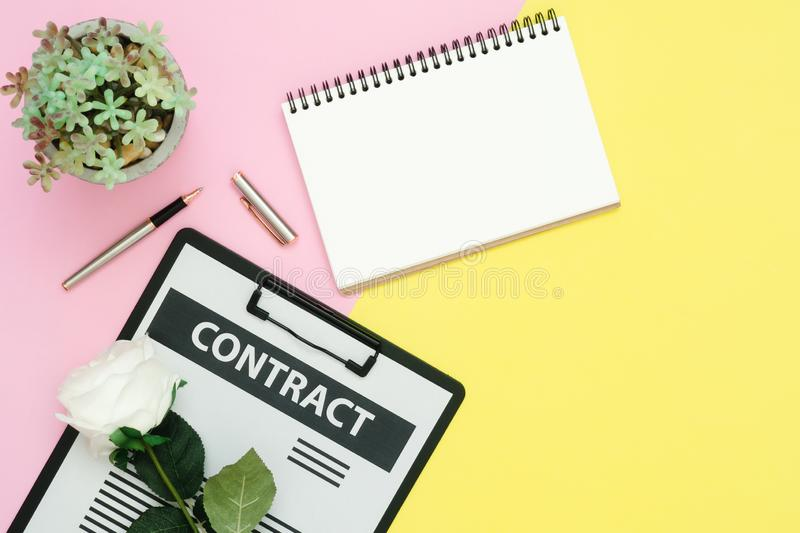 Flat lay design of working space - Top view mockup of contract document, pen and white paper notebook with rose and tree on pink. Yellow pastel color with copy stock photography