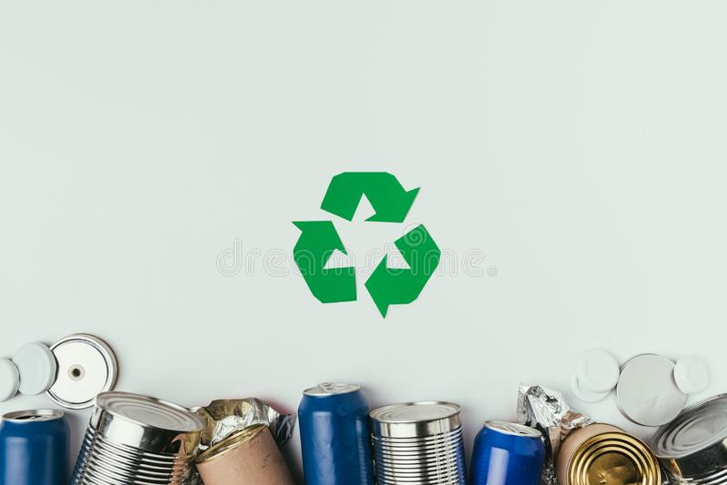 Flat lay with different cans and recycle sign isolated on grey stock photography
