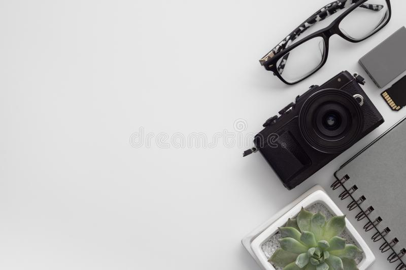 Flat lay of digital camera, battery, sd card, glasses, notebook royalty free stock images
