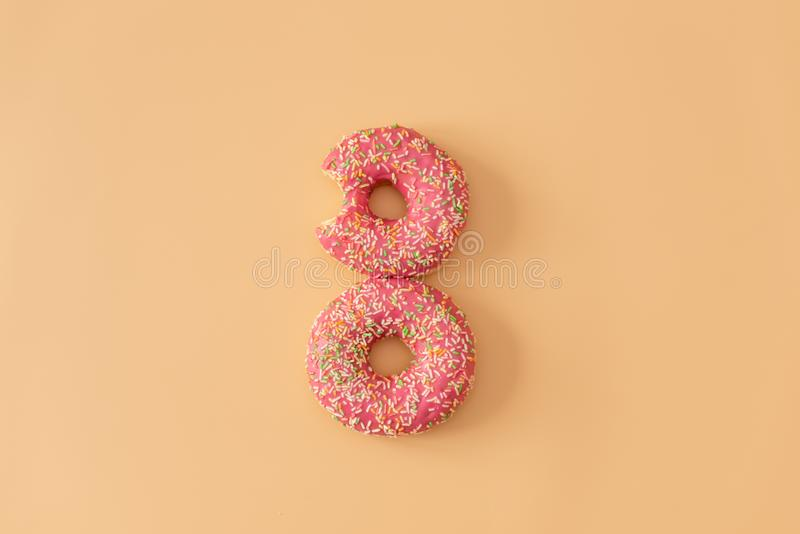Flat lay donuts pattern on pastel orange background. Top view. Square crop. Sweet doughnut texture, copy space stock images