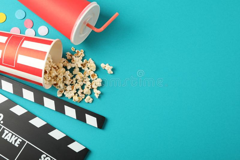 Flat lay. Drink, bucket with popcorn, clapperboard and confetti on color background. Copy space royalty free stock photography