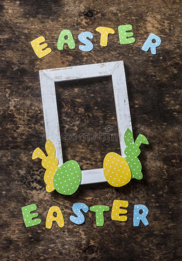 Flat lay Easter background. Empty frame, paper homemade rabbits on wooden rustic background, top view. Easter decorations. Free space for text royalty free stock images