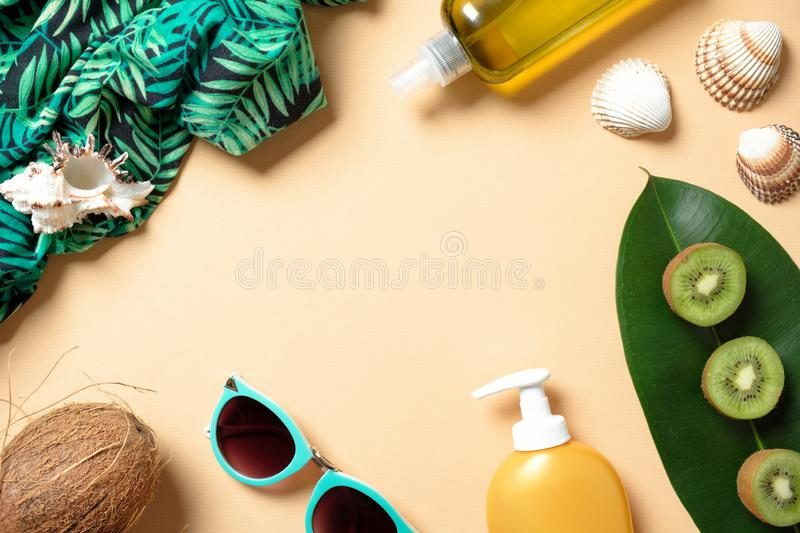 Flat lay elegance woman summer beach accessories on yellow background. Frame with feminine clothes and stuff: suntan lotion, royalty free stock image