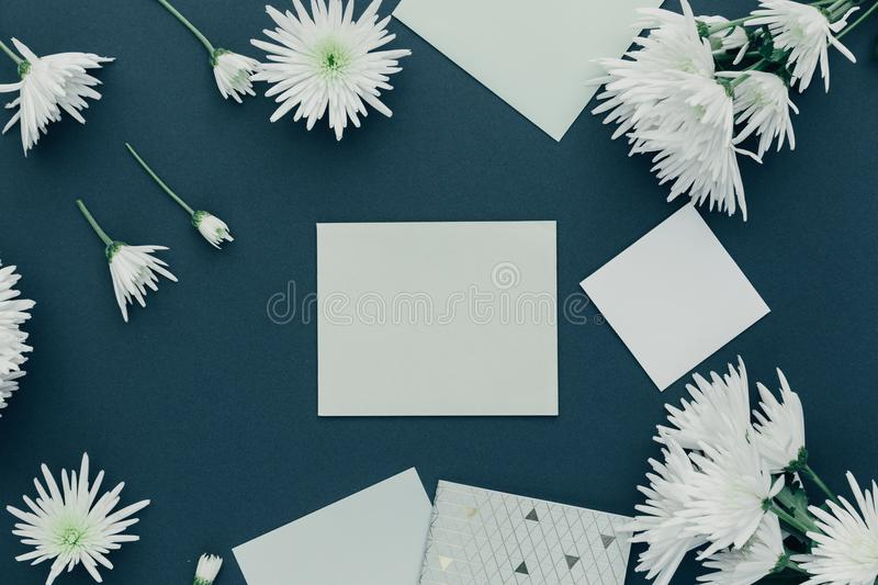 Flat lay empty card on pastel blue background. Wedding invitation cards or love letter with white flowers. stock photography