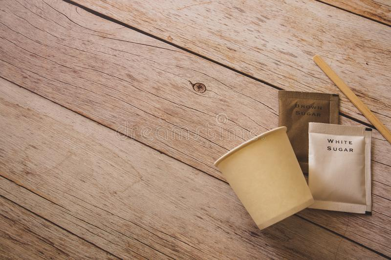 Flat lay of empty mock up white paper cup with white and brown sugar bags and wood stick on wooden table as background stock photos