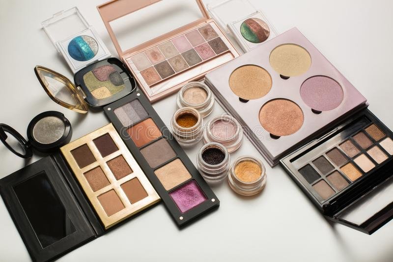 Flat lay of eyeshadow palettes, highlighters and mineral eye pig. Flat lay of professional eyeshadow palettes, highlighters and mineral eye pigments on a white royalty free stock image