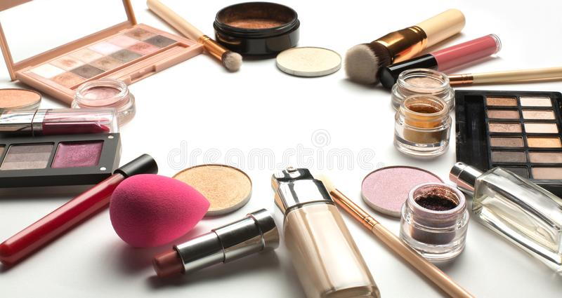 Flat lay of eyeshadow palettes, liquid foundation and lipstick o. Flat lay of professional eyeshadow palettes, liquid foundation and lipstick on a white stock images