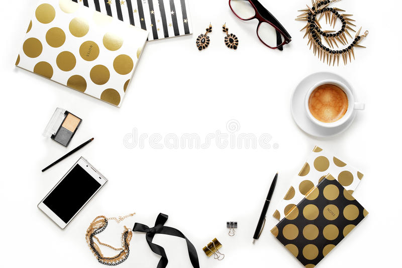 Flat lay fashion feminine home office workspace with phone, cup of coffee, stylish black gold notebooks, cosmetics and jewelry on royalty free stock photography