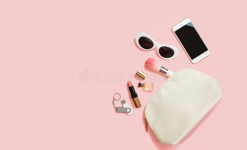 Flat lay female accessories cosmetics sunglasses mobile phone headphones flash drive makeup on pastel pink background. Valentine`s royalty free stock photography