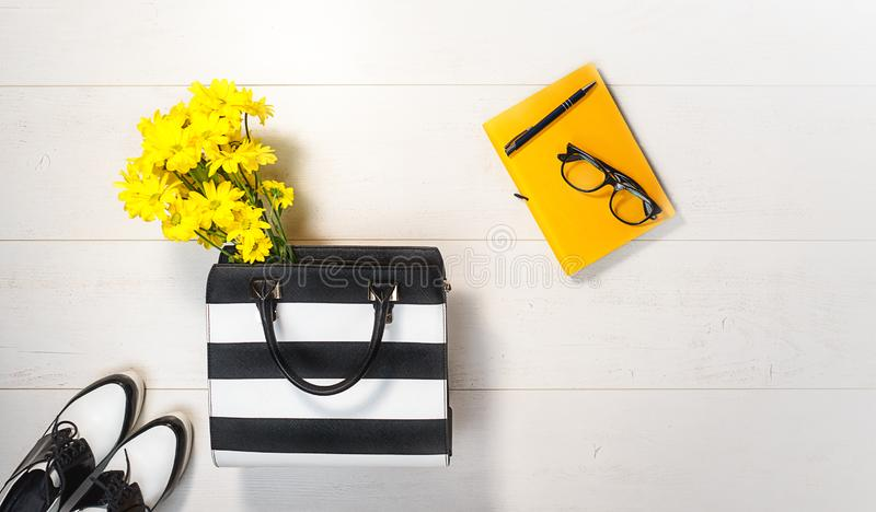 Flat lay female business accessories yellow flowers on white background. Female style with bag shoes notebook glasses pen. royalty free stock images