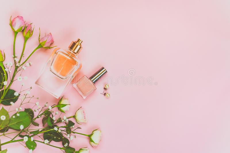 Flat lay of female cosmetics products and accessories. A bottle of perfume, nude nail polish, pearl earings and roses over pink ba. Ckground. Copy space royalty free stock images