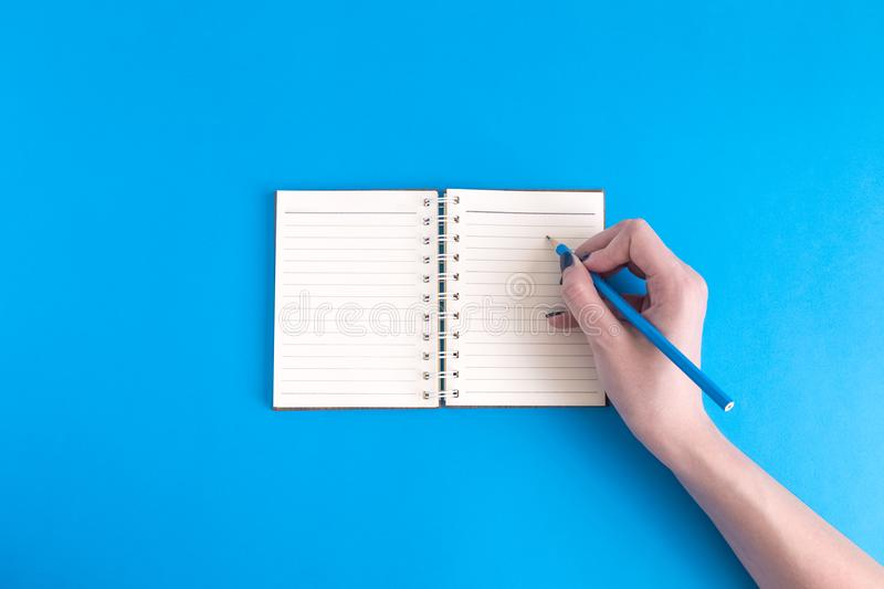 Flat lay of female hand with notepad on blue background royalty free stock photography