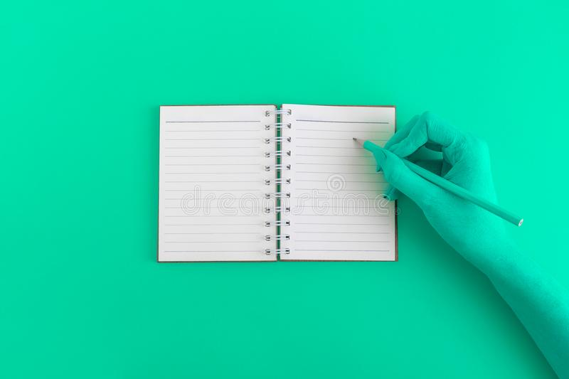 Flat lay of female hand with notepad on green background royalty free stock image