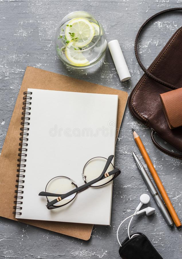 Flat lay female office desk with notepad, tablet, leather bag, glasses, earphones, lipstick and a glass of refreshing lemon thyme stock image