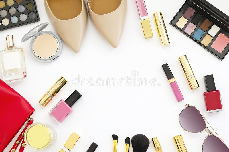Flat lay feminine accessories collage with beige high heel shoes, sunglasses and cosmetics set on white background. Text space. Be royalty free stock image