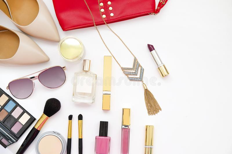 Flat lay feminine accessories collage with beige high heel shoes, sunglasses and cosmetics set on white background. Text space. Be royalty free stock images
