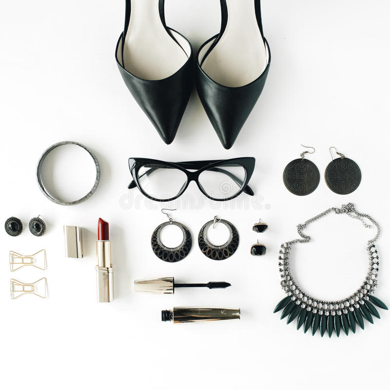 Flat lay feminine accessories collage with glasses, high heel shoes, mascara, lipstick, bracelet, earrings, necklace and bow tie royalty free stock photography