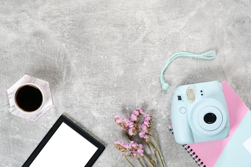 Flat lay feminine accessories: instant film camera coffee cup, dry flowers and e book reader on concrete surface. Top view beauty. Blogger workspace, freelancer stock photos