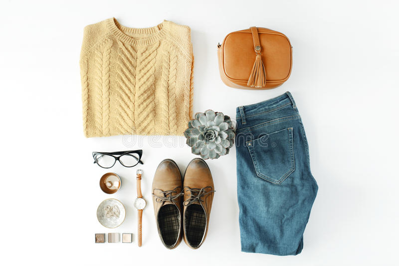 Flat lay feminine clothes and accessories collage with brown cardigan, jeans, glasses, watch, earrings, purse, boots and succulent royalty free stock images
