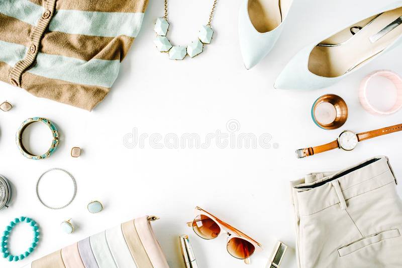 Flat lay feminine clothes and accessories collage with cardigan, trousers, sunglasses, watch, bracelet, lipstick, mint high heel royalty free stock image