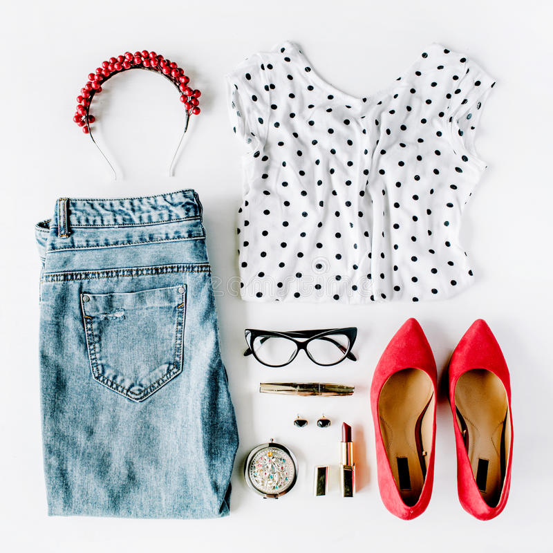 Flat lay feminine clothes and accessories collage with shirt, jeans, glasses, mascara, lipstick, red high heel shoes, earrings and stock photo