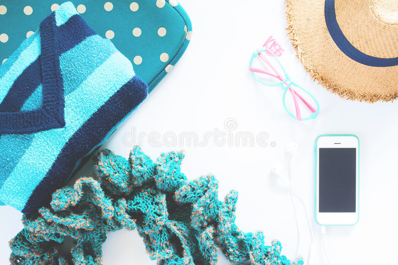 Flat lay feminine clothes and accessories collage with t-shirt, hat with mobile phone and earphone on white backg royalty free stock photos