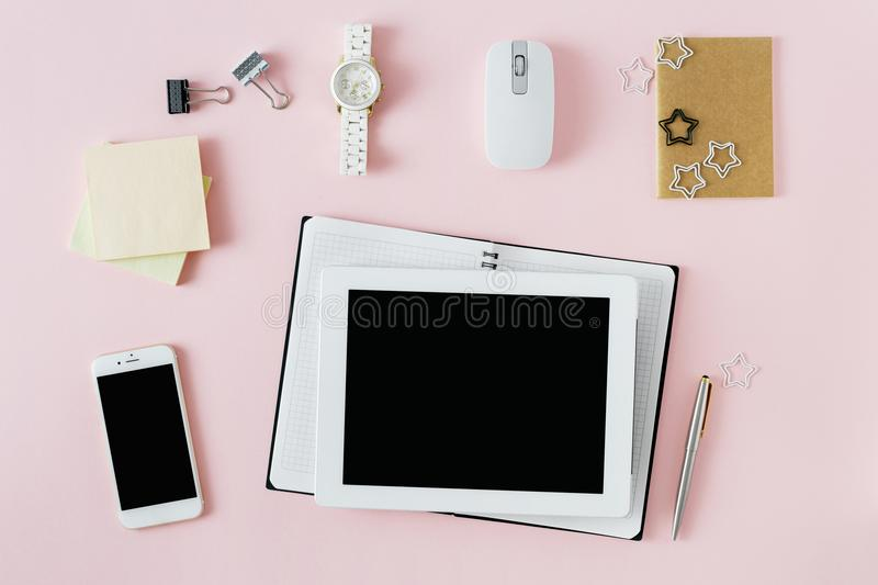 Flat lay feminine workspace tablet notebook smart phone hand wrist watch computer mouse Stylish female office table top view royalty free stock images