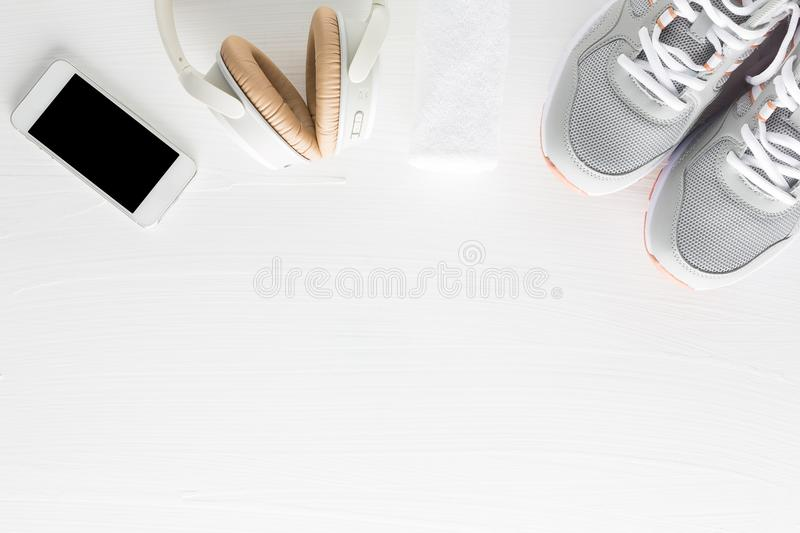 Flat lay of fitness accessories on white wooden background. Running shoes, towel, smartphone and headphone from top view. royalty free stock images