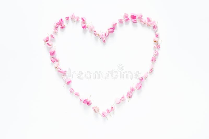Flat lay of floral heart made from pink flowers isolated on white background, top view. flower creative composition. Flat lay of floral heart made from pink stock photos