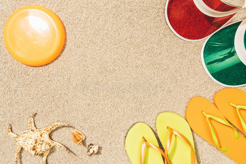 Flat lay with flying disk, colorful caps, flip flops and seashells. On sand royalty free stock images