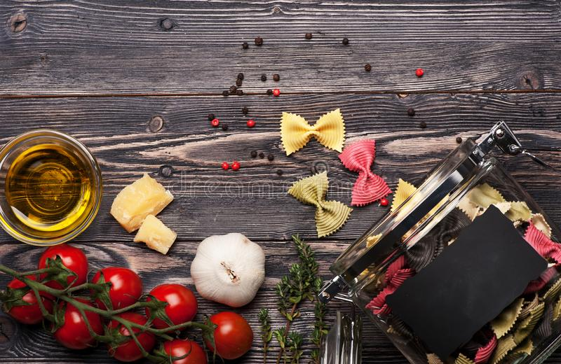 Farfalle pasta bows, garlic, parmesan cheese, tomatoes, herbs and spices royalty free stock image
