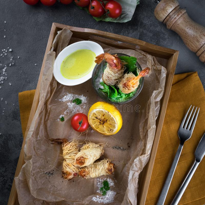 Flat lay food concept. King prawns in dough Kataifi on a wooden box on parchment paper top view. Lemon, herbs, cherry tomatoes, royalty free stock photos