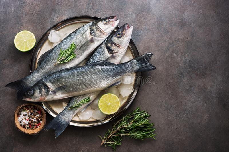 Flat lay fresh fish sea bass in a plate with ice cubes, rosemary and lime on a dark rustic background. Top view, copy space stock photo