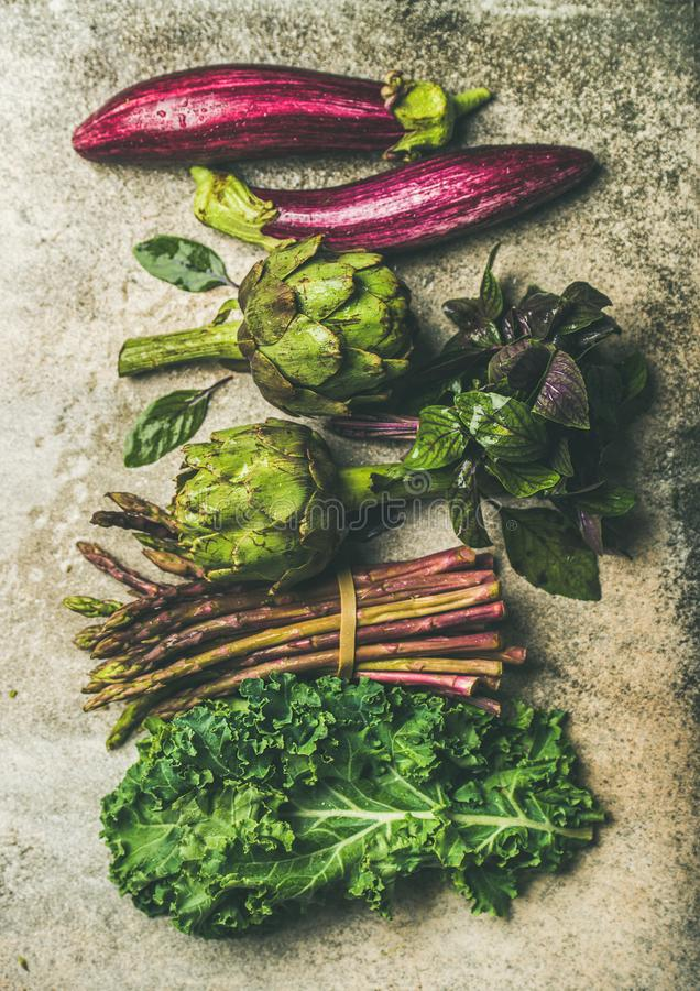 Flat-lay of fresh green and purple vegetables, vertical composition stock photo