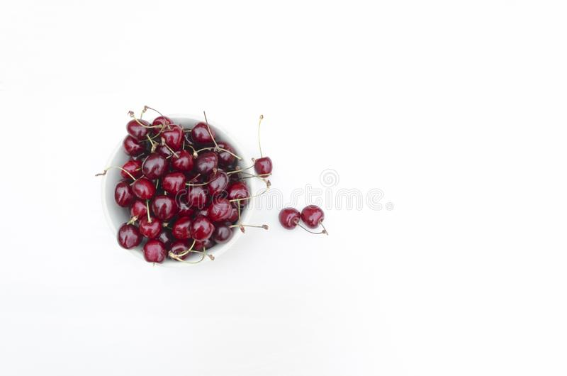 Flat lay fresh ripe sweet cherry in a glass plate. cherries. cherry on the bowl on white background. royalty free stock photo
