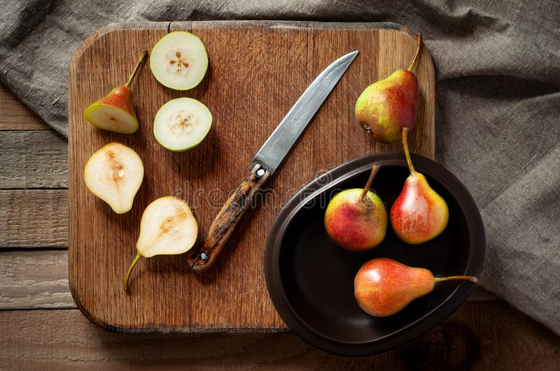 Flat lay of fresh and sliced pears in clay plate with sackcloth on wooden cutting board. Still life in rustic style. stock image