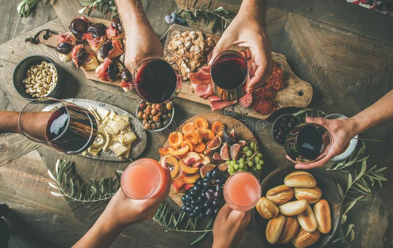 People having party sitting at table set with wine snacks. Flat-lay of friends eating and drinking together. Top view of people having party, gathering, dinner royalty free stock photos