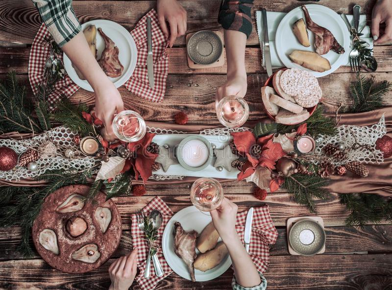 Flat-lay of friends hands eating and drinking together. Top view of people having party, gathering, celebrating together at wooden royalty free stock photography
