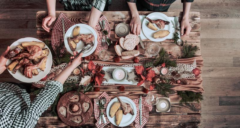 Flat-lay of friends hands eating and drinking together. Top view of people having party, gathering, celebrating together at wooden royalty free stock photo
