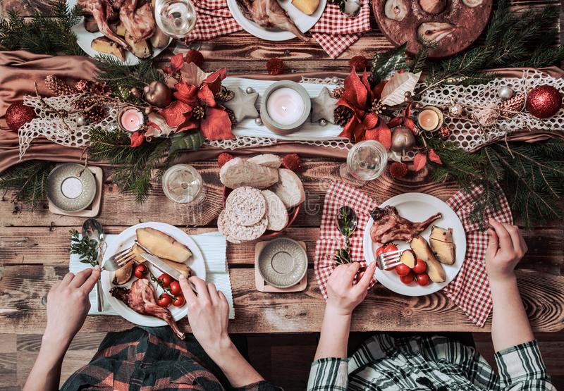 Flat-lay of friends hands eating and drinking together. Top view of people having party, gathering, celebrating together at wooden stock image
