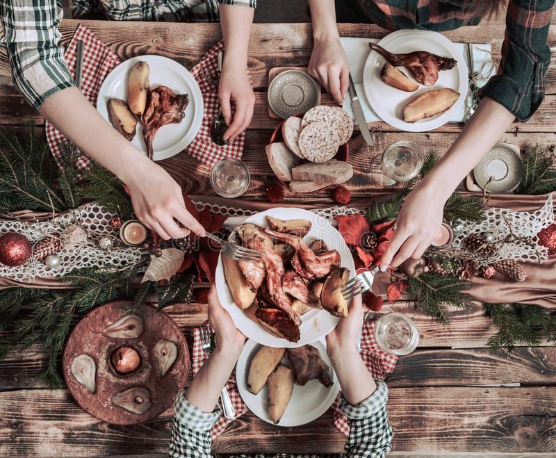 Flat-lay of friends hands eating and drinking together. Top view of people having party, gathering, celebrating together at wooden stock photos