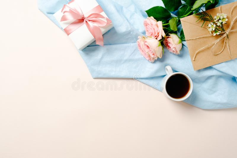 Flat lay gift box, coffee cup, rose flowers bouquet, kraft paper envelope and blue textile cloth on pastel pink background with royalty free stock photo
