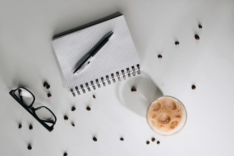 flat lay with glass of cold iced coffee, roasted coffee beans, eyeglasses, empty notebook and pen royalty free stock photo
