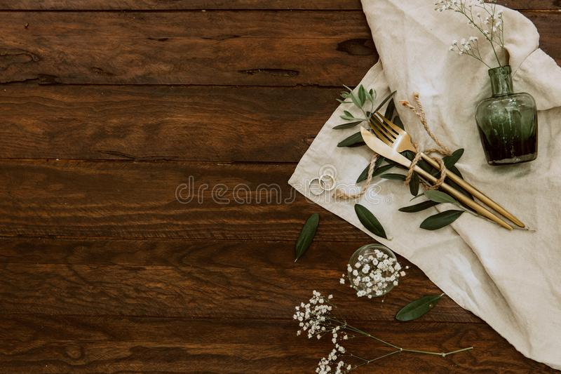 Flat lay gold cutlery, flowers, rings on linen napkin, wedding concept, holiday flowers on wooden royalty free stock photos
