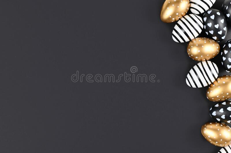 Flat lay with golden, black and white easter eggs painted with stripes, hearts and dots on black background with blank copy space. Flat lay with golden, black stock images