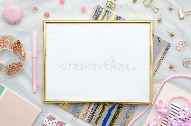 Flat lay with golden frame, and office supplies on white background. Top view pink mockup. Flat lay with golden frame, and office supplies on white background royalty free stock photography