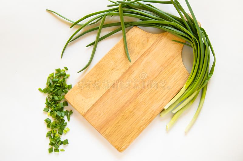 Flat lay green onion feather and sliced pieces on cutting wooden Board isolated on white background, organic food concept, copy royalty free stock images