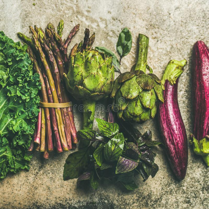 Flat-lay of fresh green and purple vegetables, square crop stock image